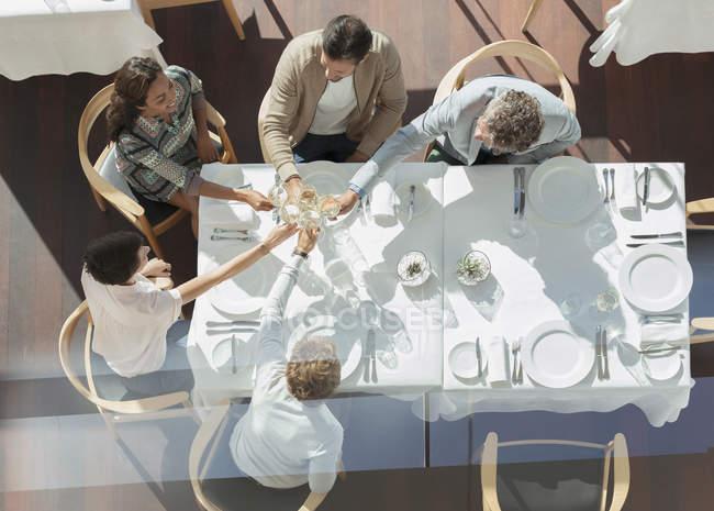 Друзья, пьющие бокалы за солнечным столиком в ресторане — стоковое фото