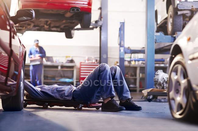 Механик под машиной в автомастерской — стоковое фото