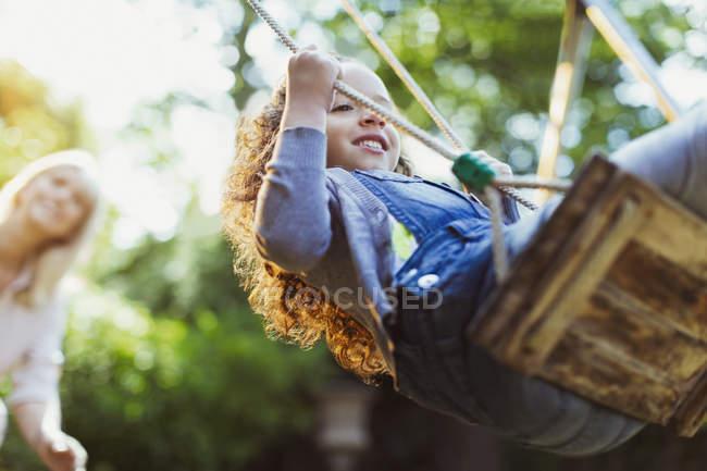 Carefree girl swinging in park — Stock Photo