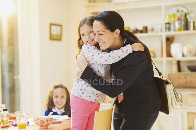 Working mother hugging daughter goodbye at breakfast table — Stock Photo