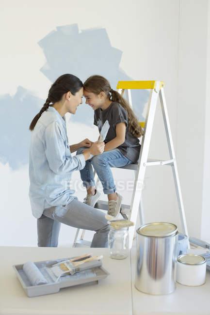 Мать и дочь рисуют стену синей — стоковое фото