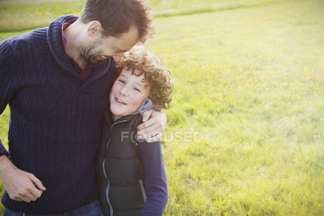 Father hugging son in field — Stock Photo