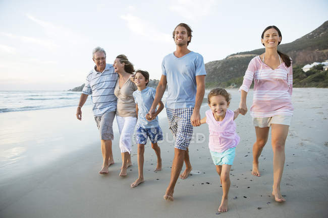 Family walking together on beach — Stock Photo