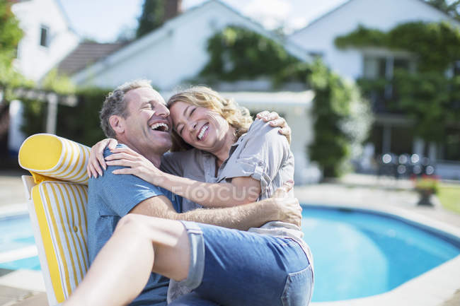 Couple relaxing in lounge chair at poolside — Stock Photo