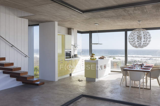 Modern kitchen and dining room overlooking ocean — Stock Photo