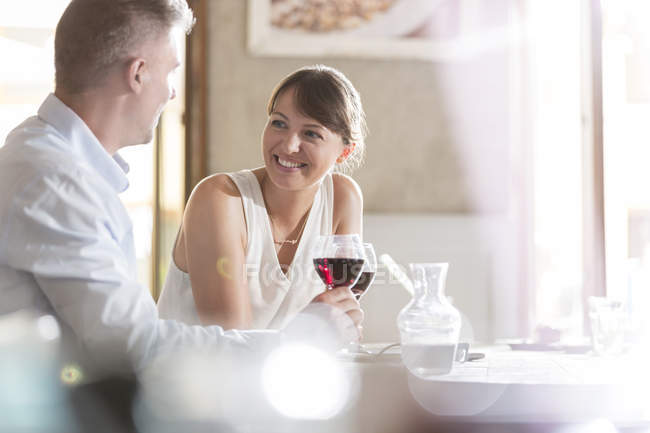 Man and woman sitting at cafe table while drinking wine — Stockfoto