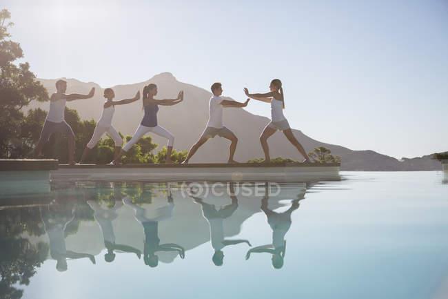 Jeunes gens attrayants pratiquant le bord de la piscine tai chi — Photo de stock
