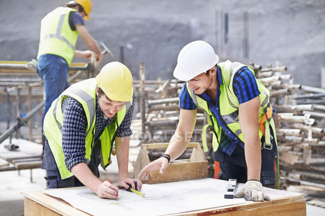 Construction worker and engineer revising blueprints at construction site — Stock Photo
