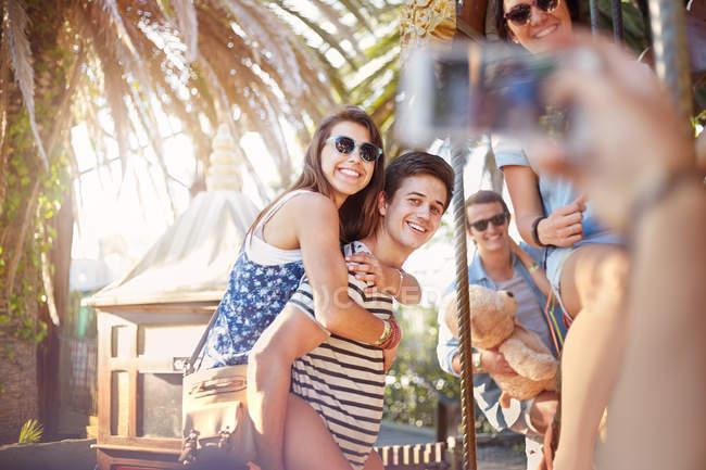 Друг фотографирует молодую пару в парке аттракционов — стоковое фото