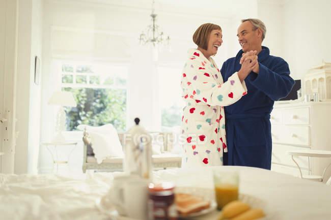 Mature couple dancing in bathrobes in bedroom — Stockfoto
