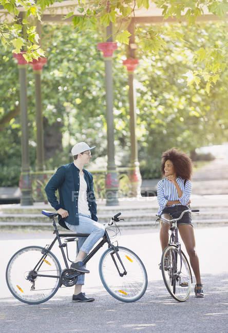 Amigos em bicicletas conversando no parque urbano — Fotografia de Stock