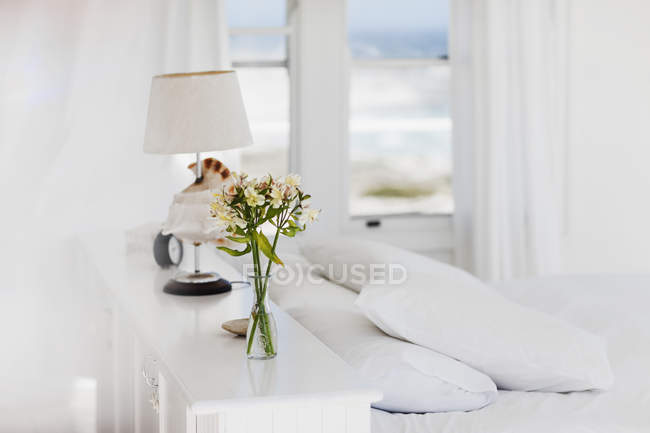 Vase of flowers and lamp in white bedroom — Stock Photo