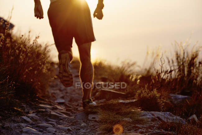 Man running on craggy trail at sunset — Stockfoto