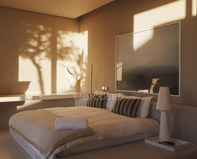 Reflection of trees on wall in modern bedroom — Stock Photo