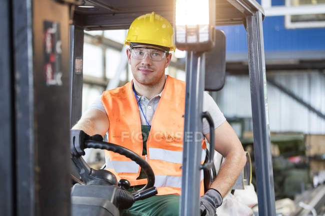 Portrait worker driving forklift in factory — Stock Photo