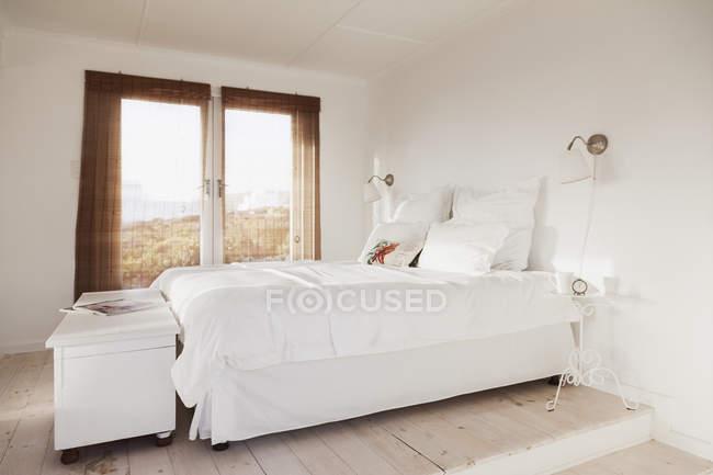 Bed in cozy white bedroom interior — Stock Photo