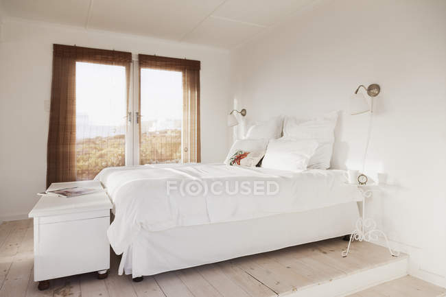 Bed in cozy white bedroom interior — Stock Photo