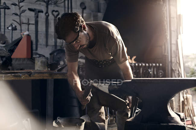 Blacksmith working at anvil in forge — Stock Photo