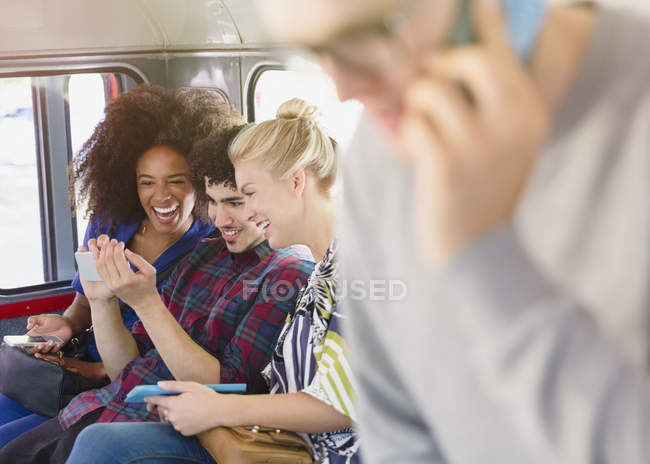 Friends texting with cell phone on bus — Stock Photo