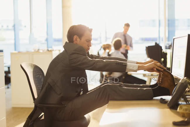 Businessman stretching feet on desk in office — Stock Photo