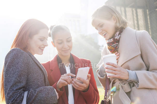Mujeres mensajes de texto y beber café al aire libre - foto de stock