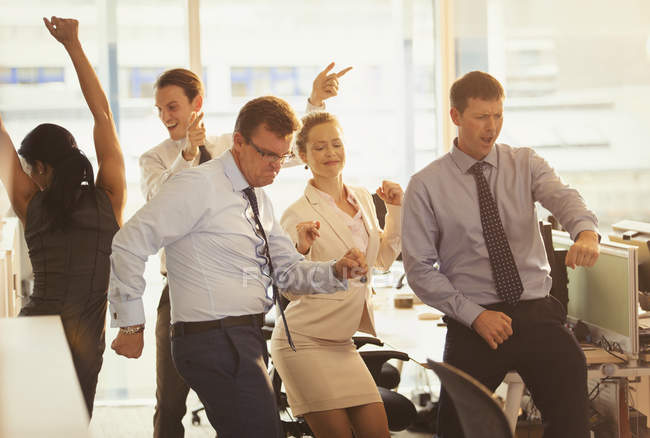 Enthusiastic business people celebrating and dancing in office — Stock Photo