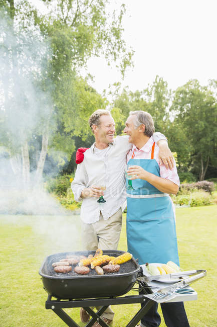 Happy men hugging at barbecue in backyard — Stock Photo