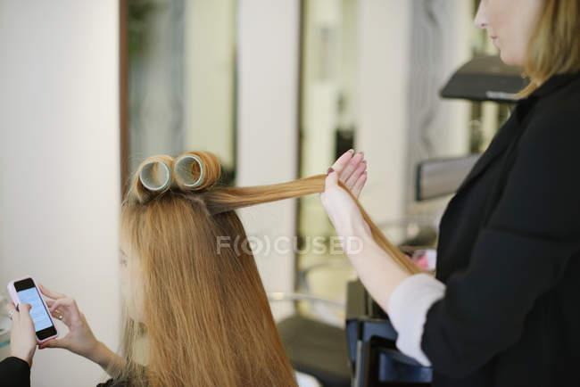 Coiffeur roulant les cheveux des clients dans les bigoudis dans le salon — Photo de stock