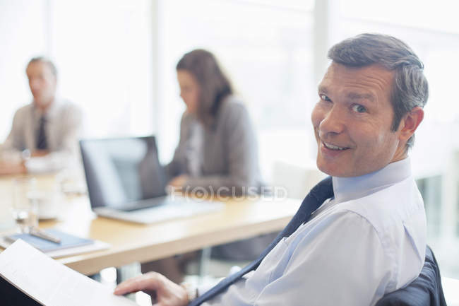 Businessman smiling in office indoors — Stock Photo