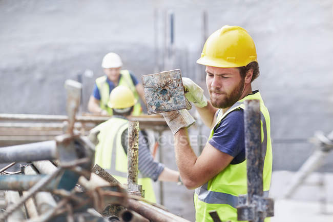 Construction worker carrying metal bar at construction site — Stock Photo