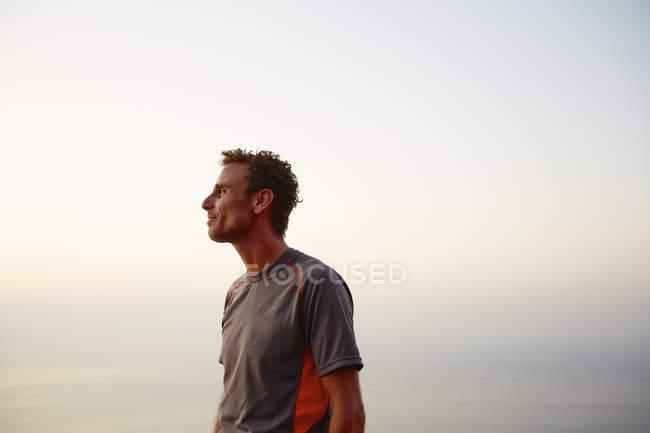Coureur faisant une pause et regardant la vue sur l'océan — Photo de stock