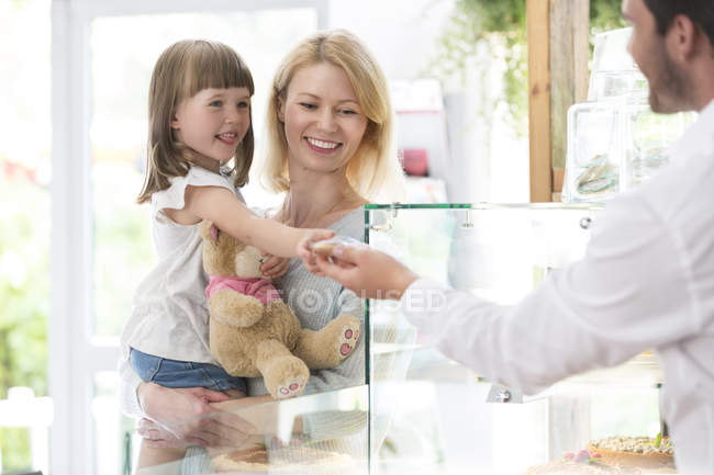 Mother with little girl on hands at shop counter — Stockfoto