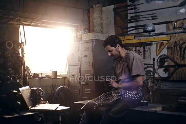 Blacksmith texting in forge at blacksmith shop — Stock Photo