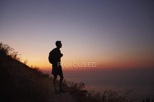 Silhueta de caminhante masculino em trilha com vista para o oceano ao pôr do sol — Fotografia de Stock