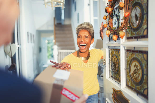 Donna entusiasta che riceve la consegna del pacchetto alla porta d'ingresso — Foto stock
