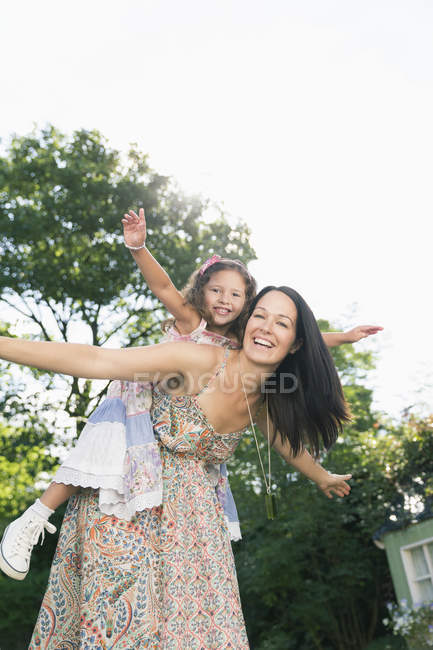 Portrait carefree mother piggybacking daughter with arms outstretched — Stock Photo