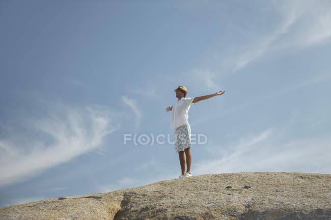 Hombre de pie sobre la formación de rocas - foto de stock