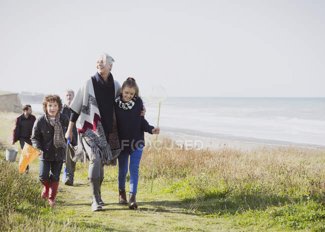Multi-generation family walking on grassy beach path — Stock Photo