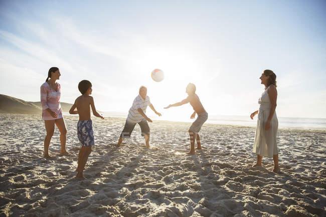 Семья из нескольких поколений играет в волейбол на пляже — стоковое фото