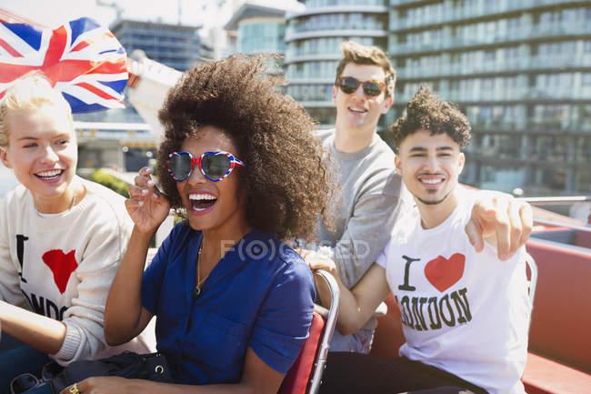 Portrait amis enthousiastes avec drapeau britannique chevauchant bus à deux étages — Photo de stock