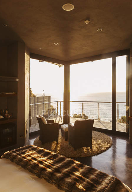 Luxury bedroom overlooking ocean at sunset — Stock Photo
