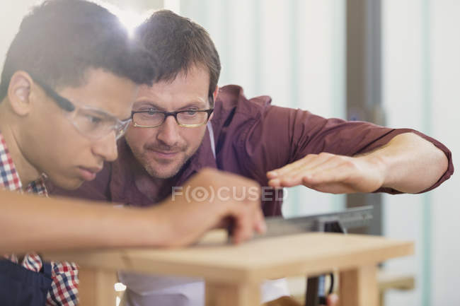 Carpentry teacher and student examining measurement — Stock Photo