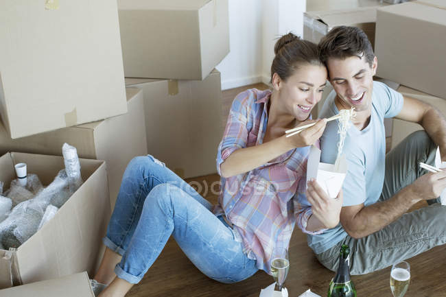 Couple sharing Chinese take out food in new house — Stock Photo