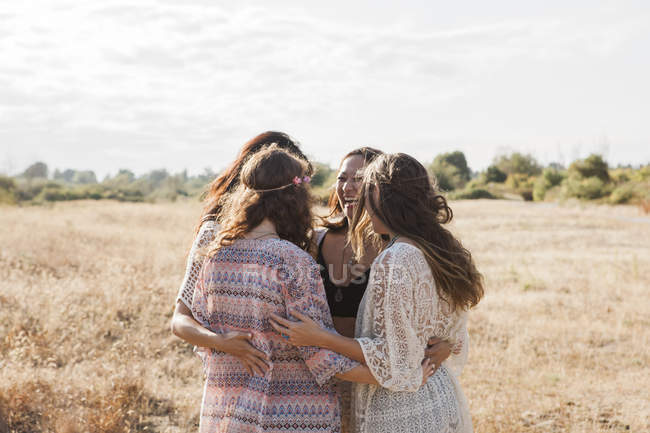 Boho women hugging in rural field — Stock Photo