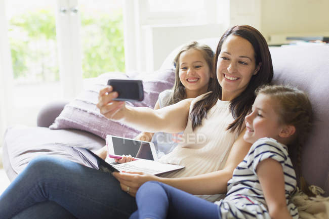 Mother and daughters taking selfie on living room sofa — Stock Photo