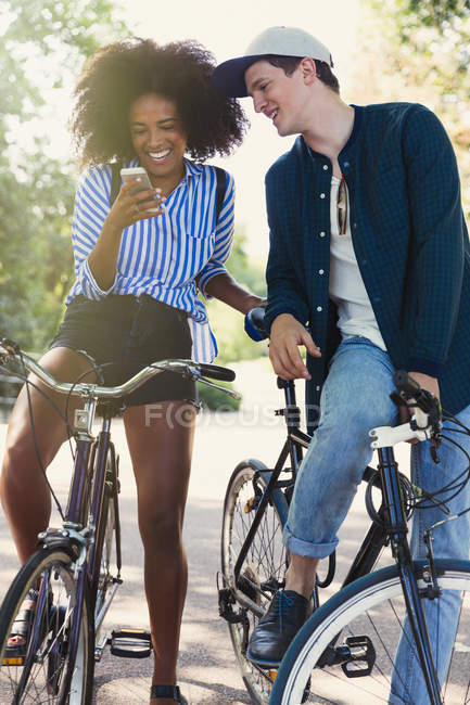 Friends on bicycles texting with cell phone — Stock Photo
