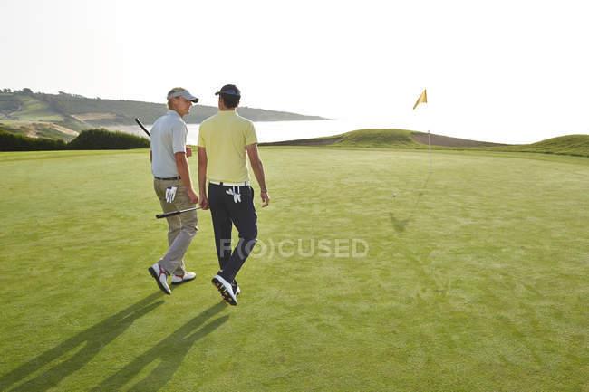 Чоловіки йшов до отвору на поле для гольфу з видом на океан — стокове фото