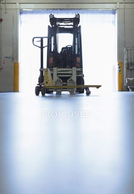 Вилочный погрузчик припаркован в дверном проеме склада — стоковое фото