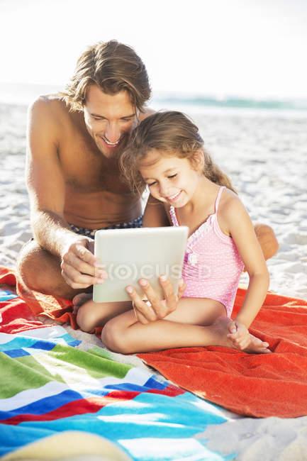 Padre e figlia utilizzando tablet digitale sulla spiaggia — Foto stock