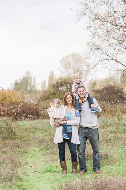 Ritratto famiglia sorridente nel parco autunnale — Foto stock